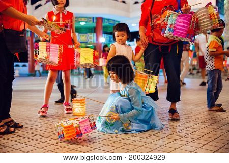 KUALA LUMPUR MALAYSIA - SEPTEMBER 15: Little girl plays with paper lanterns at Thean Hou Temple at the lantern parade during Mid-Autumn festival on September 15 2016 in Kuala Lumpur Malaysia.