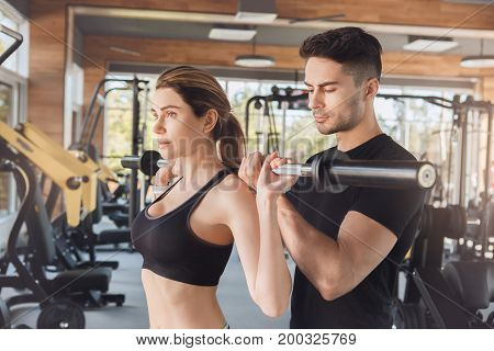 Young man and woman exercise together with barbell