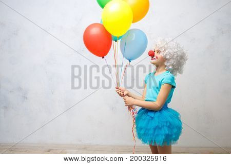 Little child wearing clown costume birthday celebration with balloons