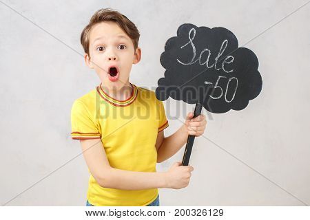 Little brunette kid isolated on white holding sale banner