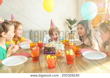 Little kids celebrating birthday together sitting at the table birthday cake