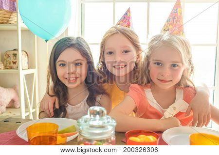 Little kids celebrating birthday together sitting at the table happy