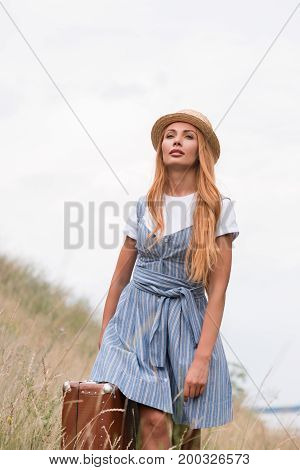 Woman With Suitcase On Grassland