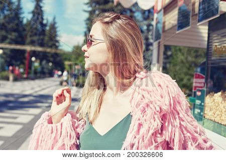 Close up shot of young blond hipster student wearing funky pink jacket smiling closing eyes with happy face expression dreaming enjoying warm summer wind while waiting popcorn in amusement park.