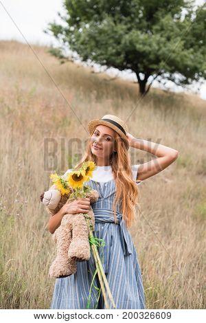Girl With Teddy Bear And Sunflowers