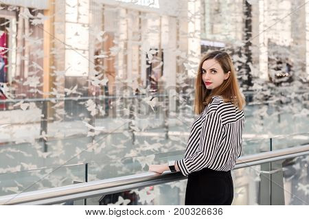Young woman with long bob hairstyle tripped blouse and black denim trousers. Portrait of young business woman. Smart casual outfit