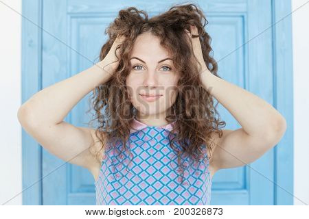 Positive human emotions. Portrait of beautiful & charming female student with messy hairstyle having shy look laughing at camera wearing stylish checkered dress touching her curvy hair with hands.
