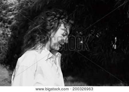 Outdoor black & white street fashion portrait of young attractive female model with curly hair wearing man's shirt looking down at her feet with the sun on her natural skin with no make up .