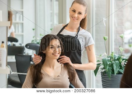 Young female sitting in hair salon hairdo styling choosing hairstyle