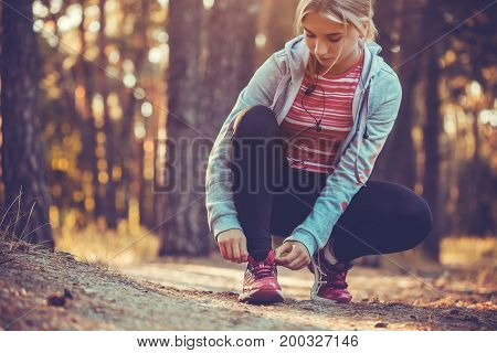 woman Runner tying shoelaces on sneakers. Morning jogging in the forest. Fitness
