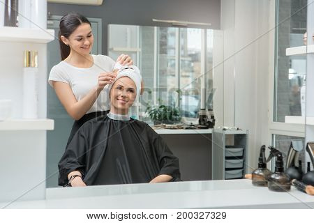 Young female sitting in hair salon hairdo styling