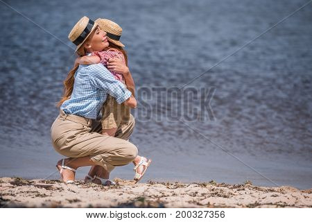 Mother And Daughter Hugging At Seashore