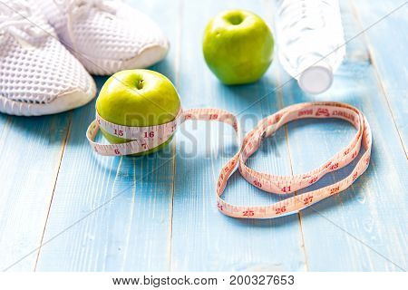 Diet and weight loss with measuring tap green apple water and sneakers for fitness on blue wooden background top view. Healthy Concept.