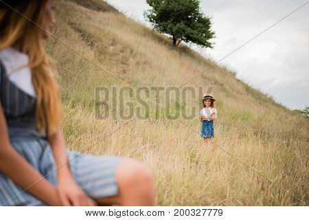 Mother And Daughter On Grassland