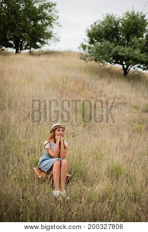 Young Woman Sitting On Suitcase