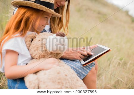 cropped shot of young mother and redhead daughter with teddy bear using digital tablet on grassland
