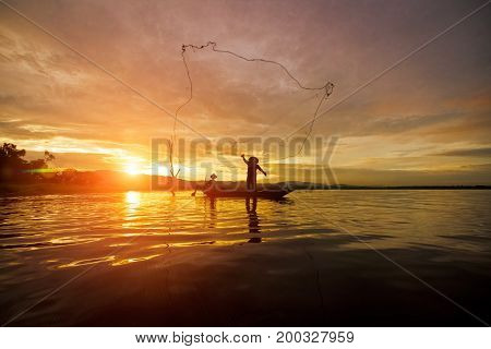 Silhouette Fisherman Fishing by using Net on the boat with sunshine in Thailand in the morning Nature and Culture concept