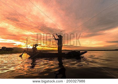 Silhouette Fisherman Fishing by using Net on the boat in morning in Thailand Nature and culture concept