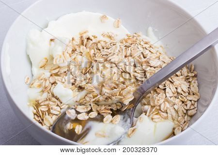 A white plate half full with oats with yogurt and honey with a spoon inside.