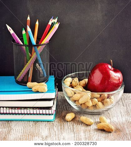 Chalk board stationery notebooks colour pencils snack nuts apple back to school and learning concepts selective focus