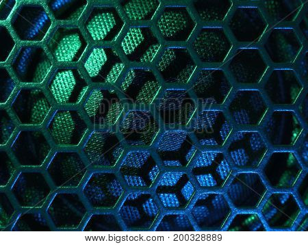 full frame colourful illuminated detail of a metallic grid in front of a loudspeaker
