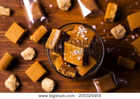 Homemade caramel candy with salt and sugar on a wooden background. Selective focus.