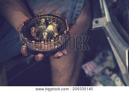 Hand holding motorcycle parts, related power supply.