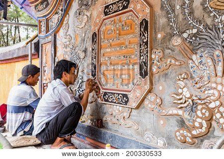 HUE VIETNAM - March 16 2017. The restorers repair the mosaic of the tomb. of Tu Duc emperor in Hue Vietnam. A UNESCO World Heritage Site. Hue Vietnam