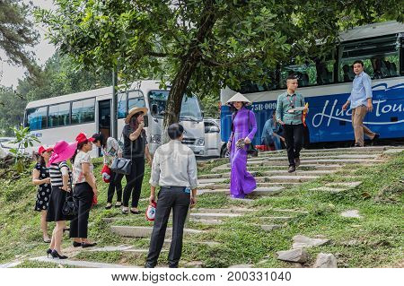 HUE VIETNAM - March 16 2017. A beautiful Vietnamese woman in a purple dress with a hat descending the stairs near Hue Vietnam