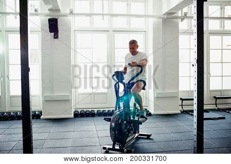 Smiling Mature Man Exercising On A Health Club Stationary Bike