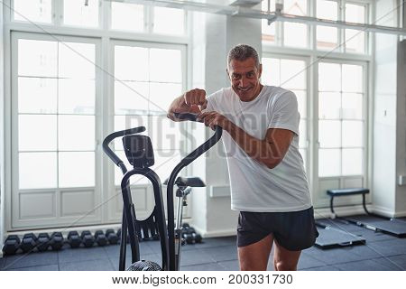 Smiling Mature Man Leaning On A Health Club Stationary Bike