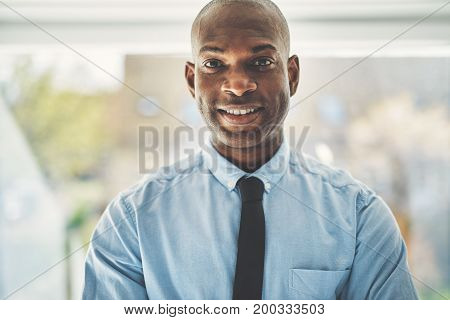 Smiling African Businessman Standing Alone In An Office