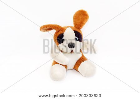 Soft white and brown toy dog. Sitting on a white background. Isolated