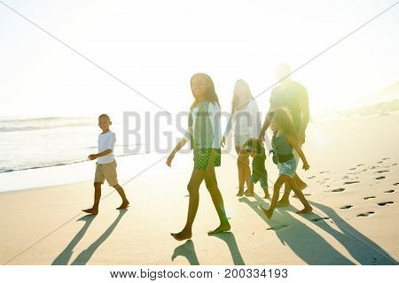 Smiling happy African-American people with their children taking walk on sunny beach.