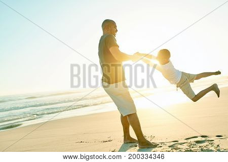 Cheerful black man spinning his son while playing on beach in evening.