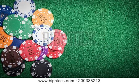 Gambling chips and cards on a green cloth Casino table