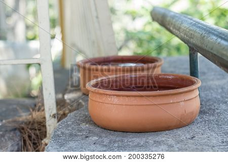 Two brown bowls made out of clay put on a grey concrete base full of water for animals to drink in a garden during the hot summer