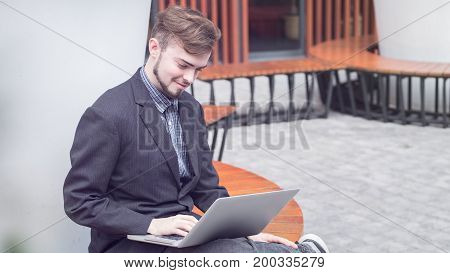Looking for direction and inspiration Portrait of happy young businessman sitting with laptop at coffee shop