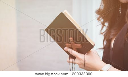 Closeup on a young asian woman holding a bible and pray believe concept