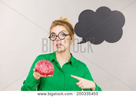Business woman wearing green jacket and eyeglasses being rude and mad solution holding fake brain black thinking or speech bubble next to her.
