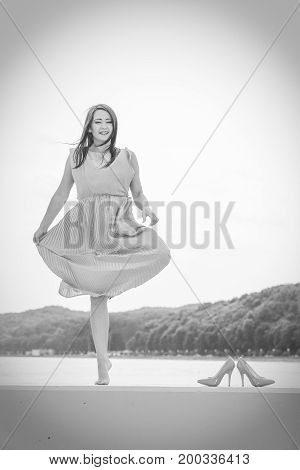 Hobby idyllic aspects of femininity concept. Woman dancing on jetty without shoes wearing beautiful long dress. Black and white photo outside.