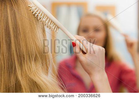 Woman Brushing Her Long Hair In Bathroom