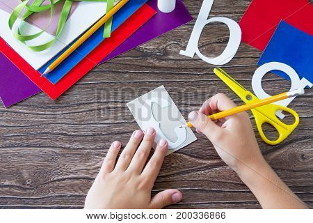 The Child Draws Details Of The Application. Greeting Card With A Pencil And Letters For The New Scho