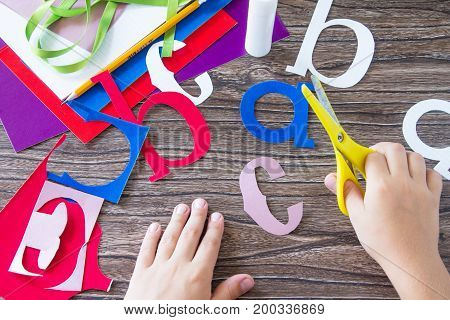 The Child Cuts Out The Alphabet Details Of The Application. Greeting Card With A Pencil And Letters