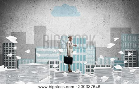 Business woman in suit standing among flying paper planes with sketched cityscape view on background. Mixed media.