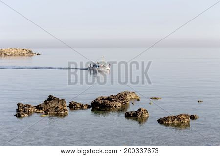 Morning at sea, fishing boat sailing in the distance(Greece, Crete Island)