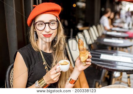 Young stylish woman in red beret having a french breakfast with coffee and croissant sitting oudoors at the cafe terrace