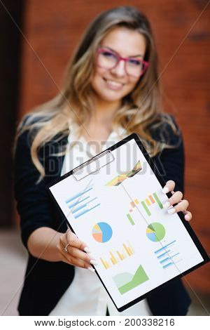 A girl in a jacket and glasses shows a tablet with diagrams