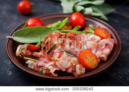 Fried Bacon And Tomatoes In Plate On A Dark Background.