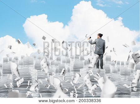 Businessman in suit standing on pile of documents among flying papers with speaker in hand with cloudly skyscape on background. Mixed media.